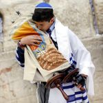 A 13-year-old Jewish boy pays respect to the Torah. (Ministry of Tourism photo taken by Yonatan Sindel, Flash 90)