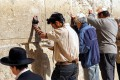 Jewish men pray in the men's section at the Western Wall.