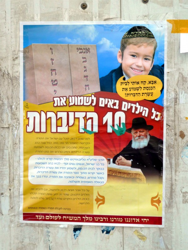 "The boy in this Jerusalem Shavuot poster asks, ""Daddy, bring me to the synagogue to hear the Ten Commandments."" The rabbi below him is Rabbi Schneerson, whom many Chabad-Luvevitcher members proclaim to be Messiah. The Hebrew writing in the red box at the bottom states, ""Long Live our Master, our Teacher, and our Rabbi, King Messiah, for ever."""