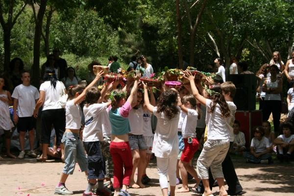 Israeli children perform a dance with offering baskets at a kibbutz on Shavuot.
