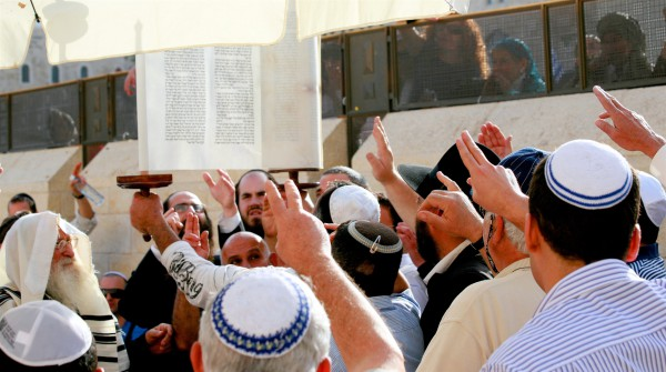 Men reach out to pay respect to the Torah as it is raised at the Western (Wailing) Wall in Jerusalem. (Photo by opalpeterliu)