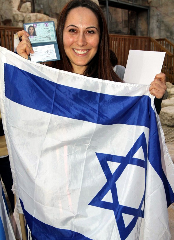 A woman holds up the Israeli flag and her new Israel identification after making Aliyah. (Jewish Agency photo by Brian Hendler)