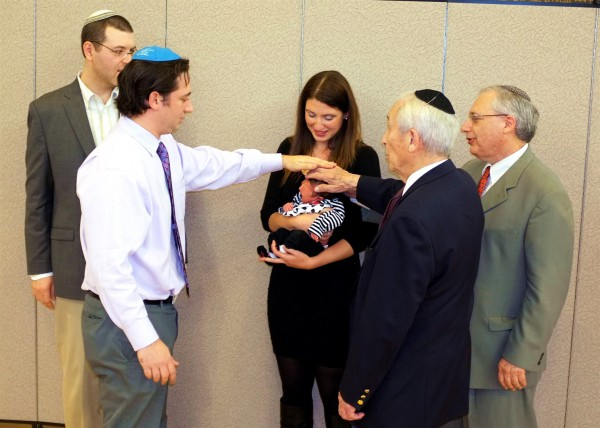 A newborn's great-grandfather, grandfather, and uncle recite the priestly blessing over her. (Photo by Avi and Elina Flax)