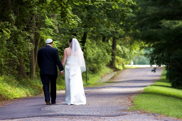 A Jewish bride and groom stroll together after the wedding ceremony.