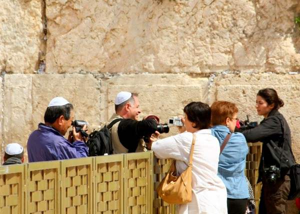 Tourists try to get a good photograph over the mechitza (barrier between the men's and women's side) at the Western Wall. (Photo by Avital Pinnick)