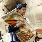 A 13-year-old Jewish boy carries the Torah scroll at the Western (Wailing) Wall. (Israel Ministry of Tourism photo by Jonathan Sindel)