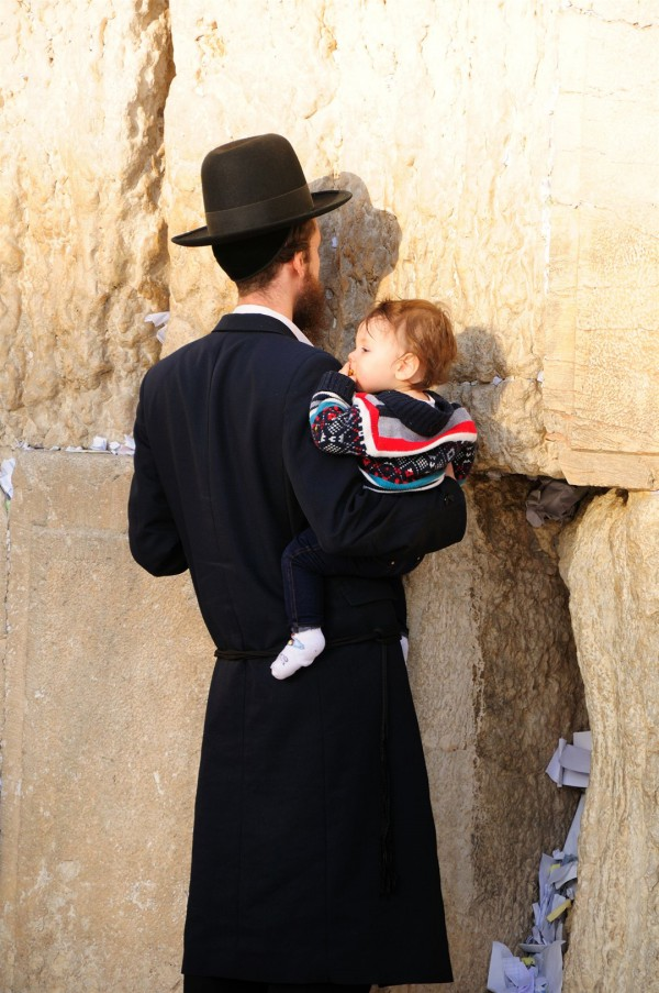 A Jewish father holds his child close as he prays at the Western (Wailing) Wall in the Old City of Jerusalem.