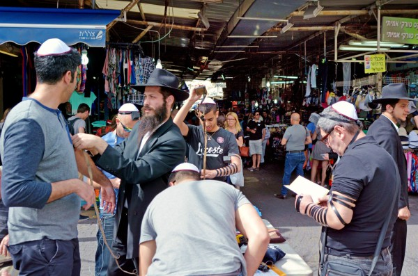 Ultra-Orthodox Jewish men in Tel Aviv show passersby how to put on tefillin (phylacteries) and pray.