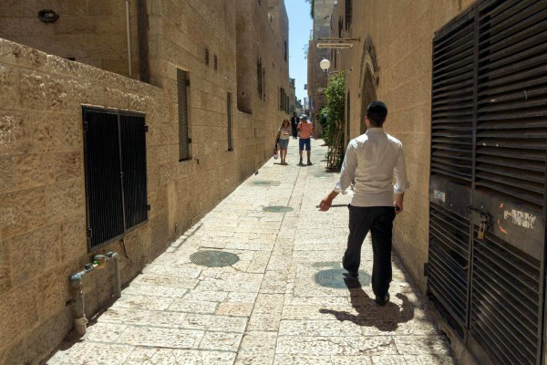 People walk down a narrow street in the Old City of Jerusalem.