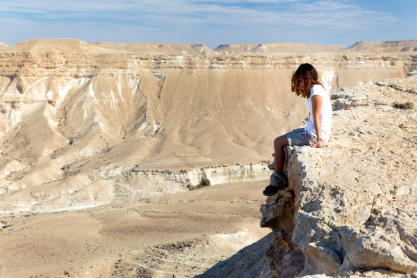 A woman sits alone in the Negev Desert.