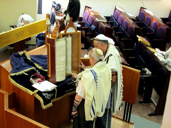 Reading from a Torah scroll encased in a protective Torah tik (case).