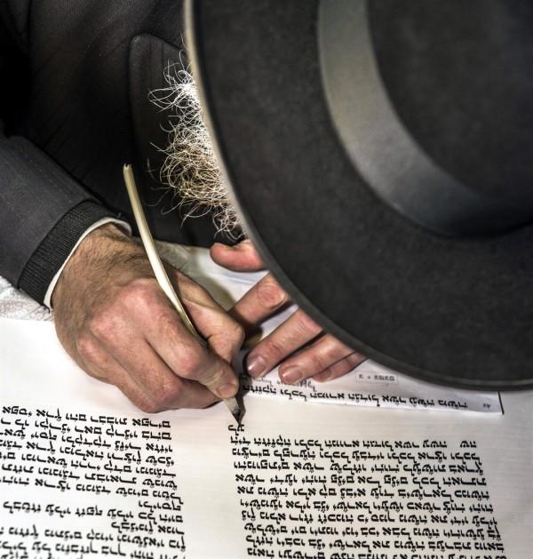 A Jewish scribe hand writes a Torah scroll.