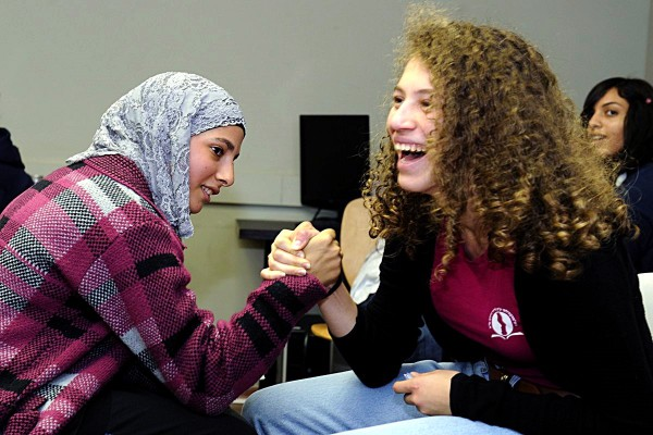 Arab and Jewish students playfully arm wrestle together. (US Embassy Tel Aviv)