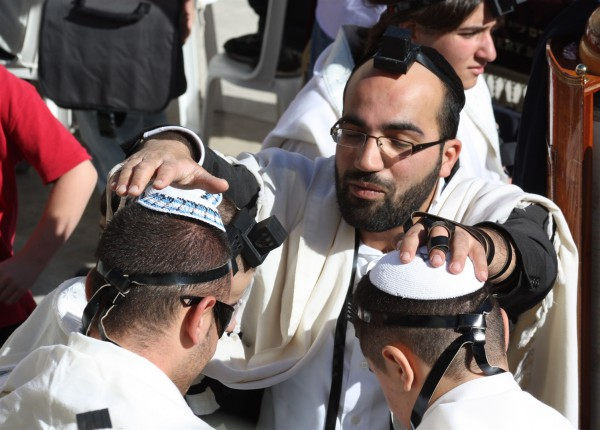 A blessing is recited over two Jewish youth at the Western Wall, also known as the Wailing Wall and the Kotel. (Photo by Kyle Taylor)