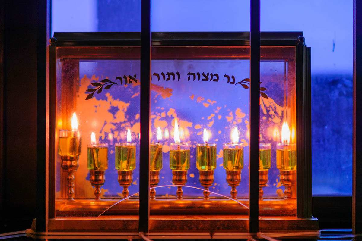 Fully lit hanukkiah (Hanukkah menorah) with oil lamps. Text on glass reads,