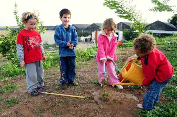 Israeli children water a tree they just planted in honor of Tu B'Shvat.