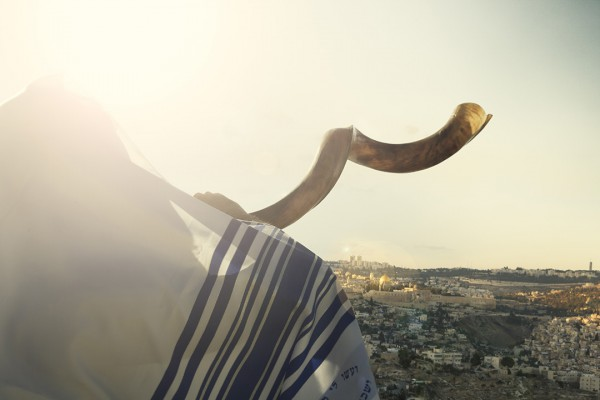 Jewish man blowing shofar over Jerusalem