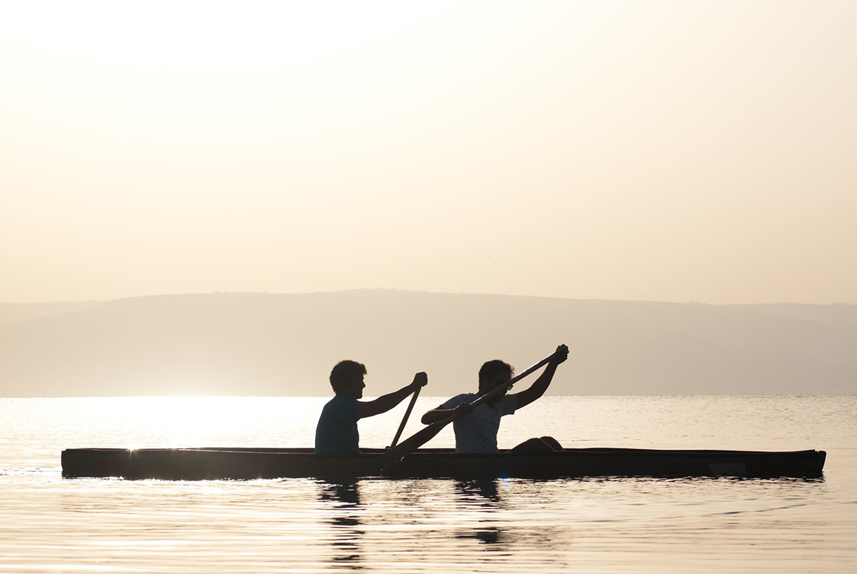 19435316 - two men paddling in a canoe at the sea of galilee