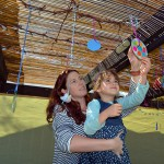 Jewish woman and child decorate their sukkah, in which they will eat, sleep, and possibly live in for the seven days of Sukkot.
