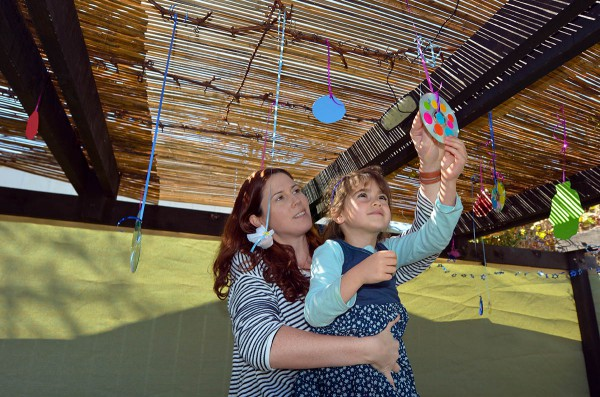 Jewish mother and daughter decorate their sukkah