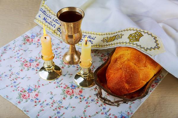 Traditional Jewish symbols of Shabbat: candles, challah bread, wine, and tallit (prayer shawl)
