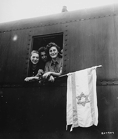 Released inmates of Buchenwald concentration camp in Germany, holding a homemade flag on their way to Israel, 1945. This design had already become the official flag of the World Zionist Organization and in 1948, the reborn state of Israel.
