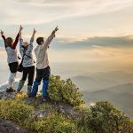 three people stand on mountain top raising hands in praise.